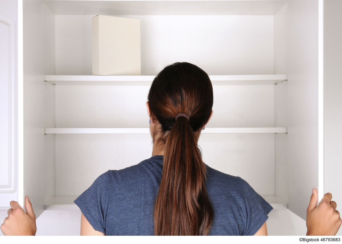 Woman staring at empty cupboard